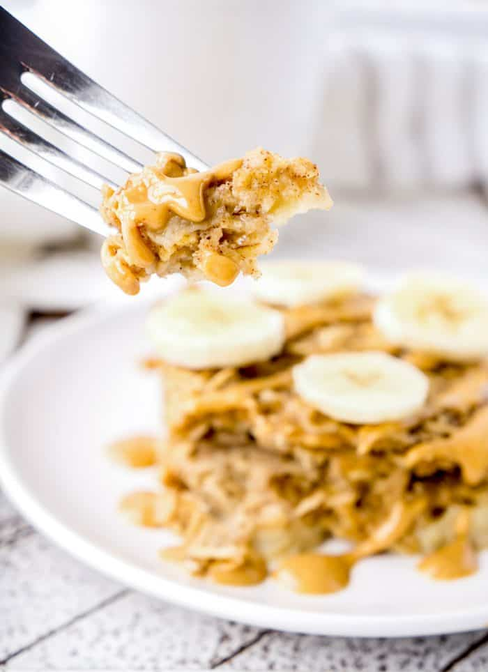 A fork holding up a piece of baked oatmeal with piece in background with banana slices
