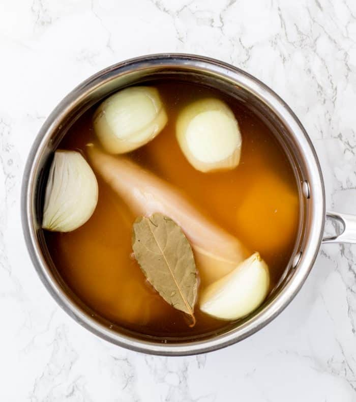 Onions, stock and bay leaves in a pot.