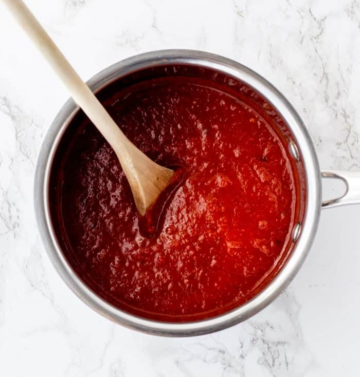 Enchilada sauce in a pot with a wooden spoon.