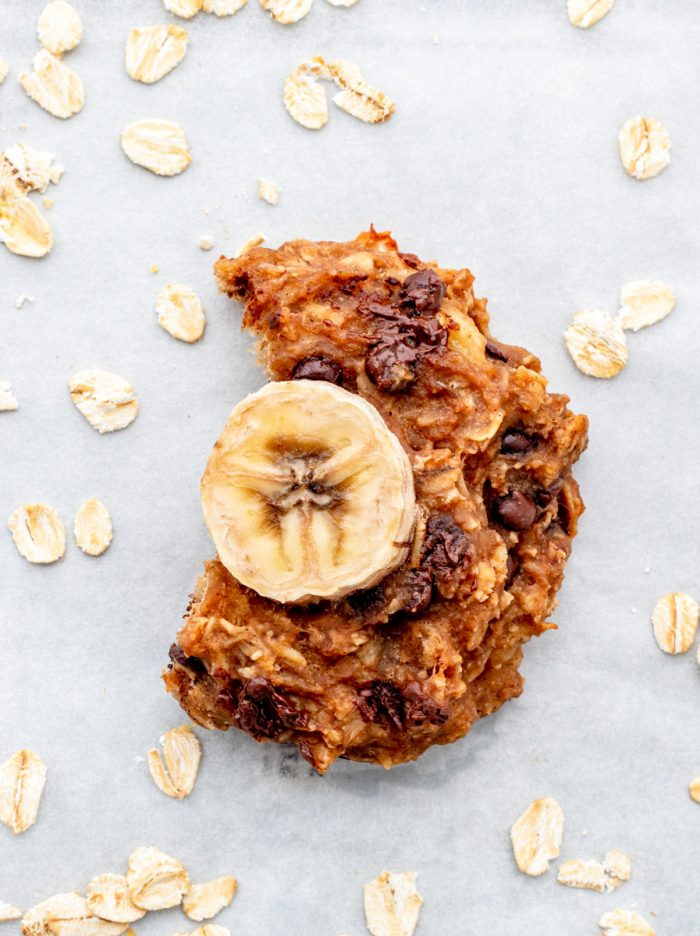 A banana oatmeal cookie with a bite taken out of it.