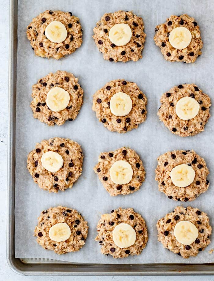 Unbaked cookies in a baking sheet, topped with a sliced banana.