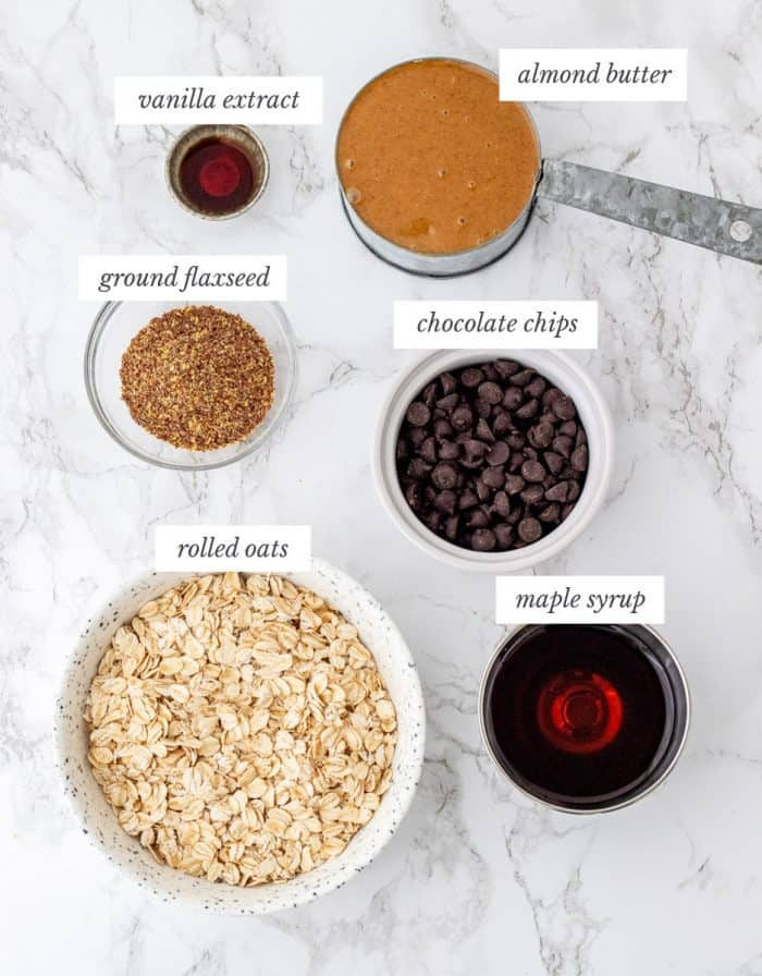 Ingredients for energy balls on marble background with labels