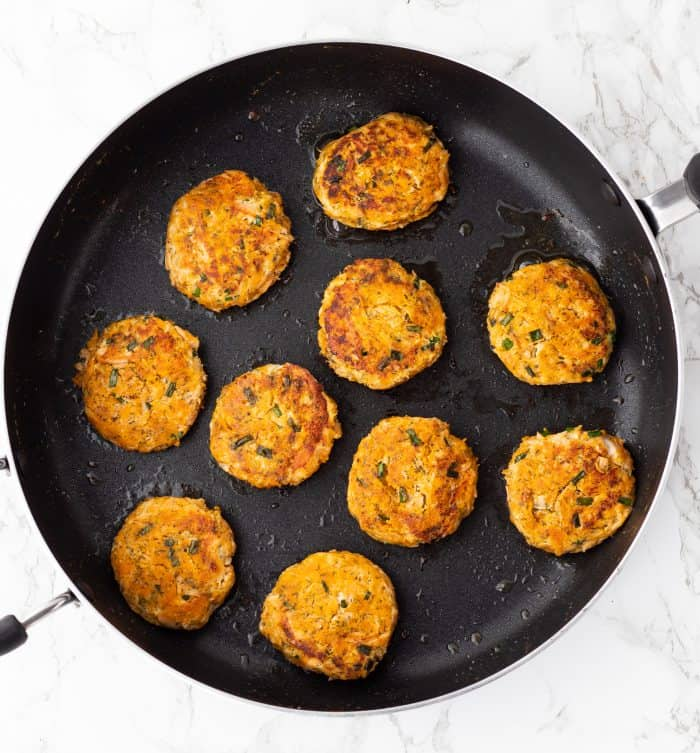 Cooked salmon cakes in a skillet.