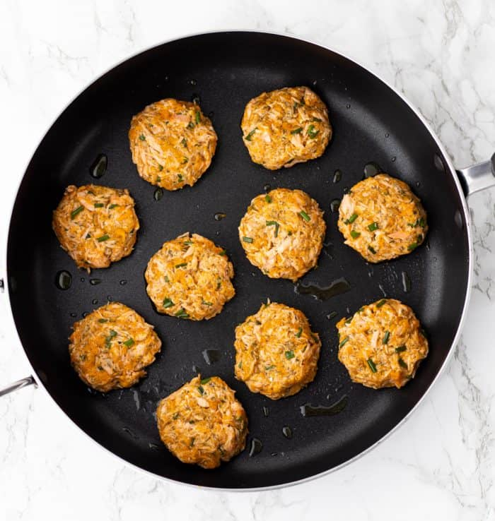 Salmon cakes cooking in a skillet.