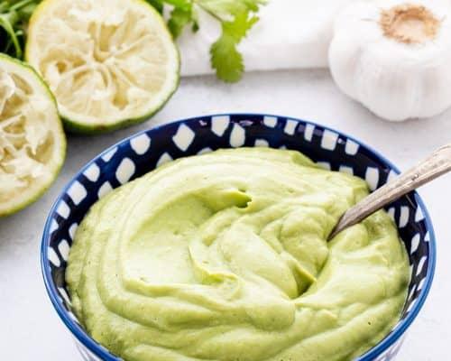 A spoon in a bowl of the vegan avocado crema.