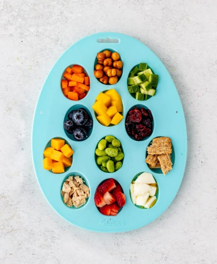 a turquoise egg shaped tray filled with bite-sized pieces of food