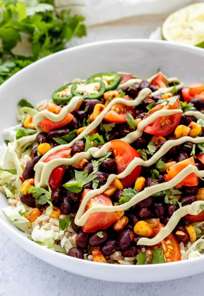 A black bean burrito bowl drizzled with sauce.
