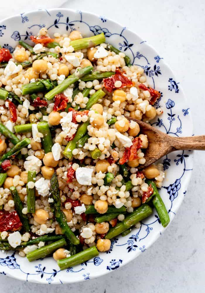 Pearl couscous salad in a blue and white bowl with a wooden spoon.