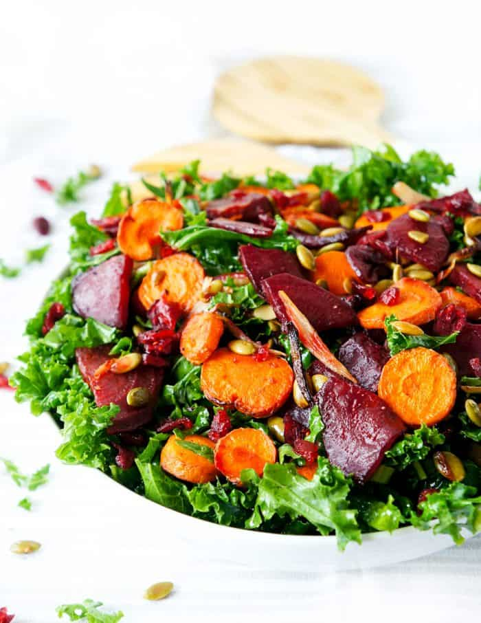Beet, carrot and kale salad served in a large white bowl.