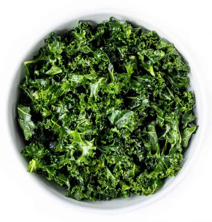 Kale massaged with oil in a white bowl.