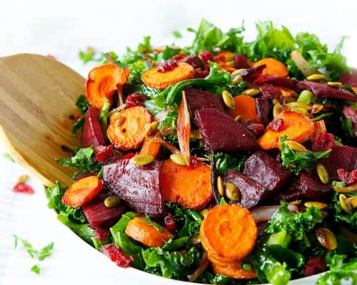 Roasted beets and carrots on a bed of kale in a white bowl with a wooden serving spoon.