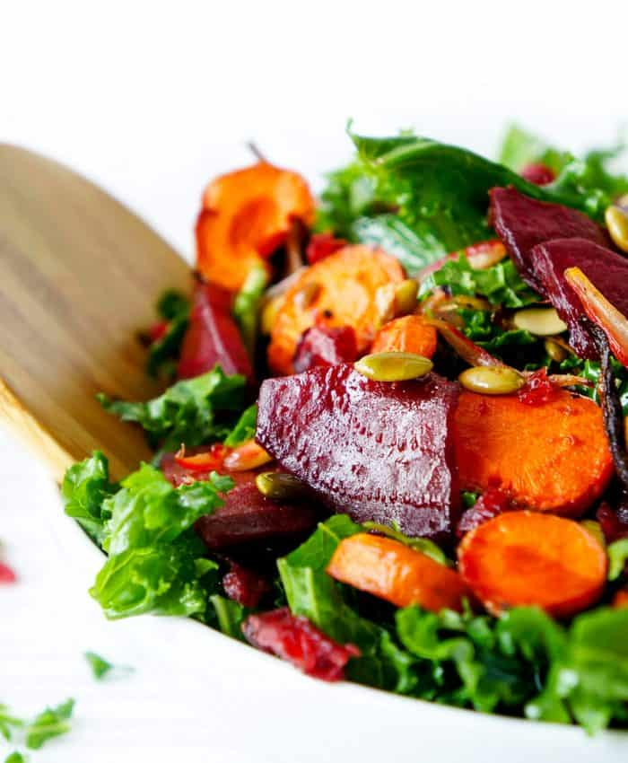 A wooden serving spoon in the bowl of carrot beet salad.