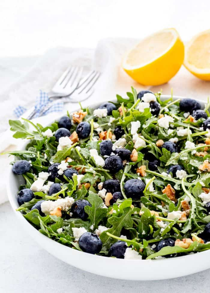 A bowl of blueberry walnut salad in front of lemon halves.