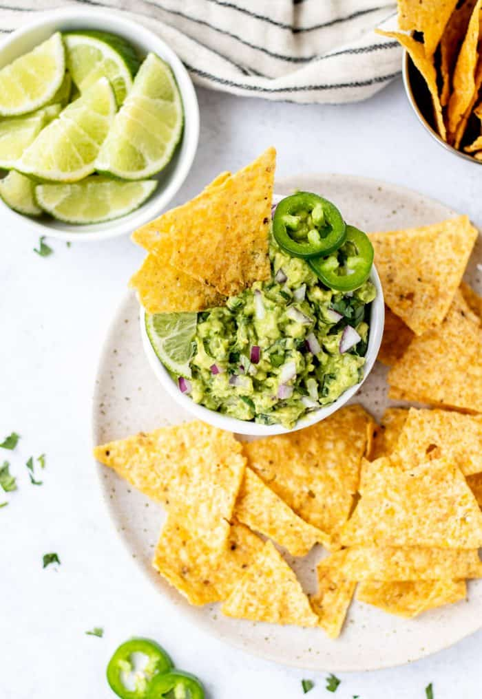A bowl of chipotle guacamole on a plate with tortilla chips.