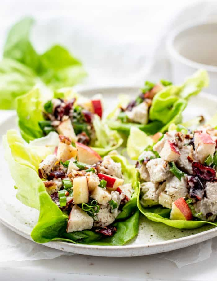 Four lettuce wraps on a white plate filled with cranberry chicken salad.