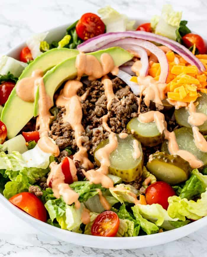 Close up of the ground beef drizzled with big mac sauve on top of a bed of salad.