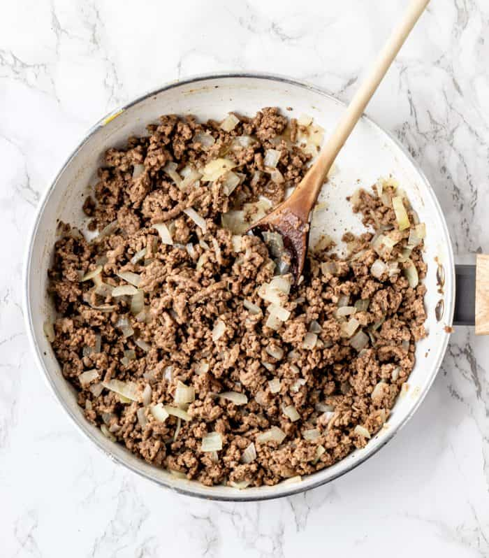 Cooking the ground beef and onions in a skillet.