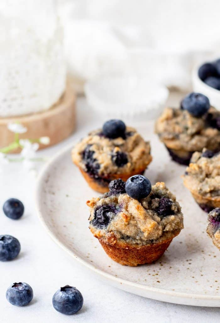 mini blueberry banana muffins on a plate next to small white flowers and fresh blueberries