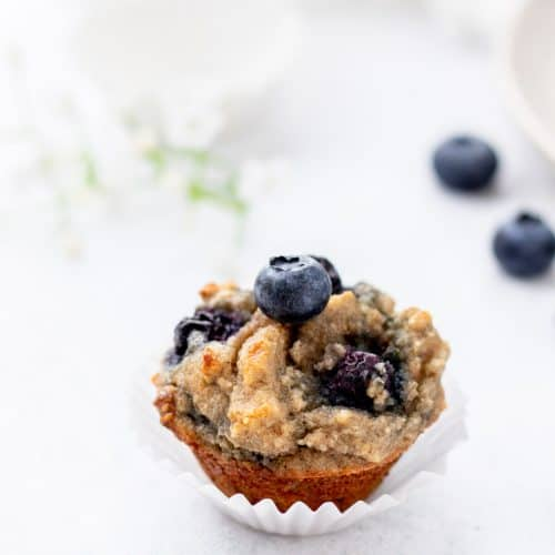 a mini almond flour blueberry muffin in a white paper liner with fresh blueberry on top