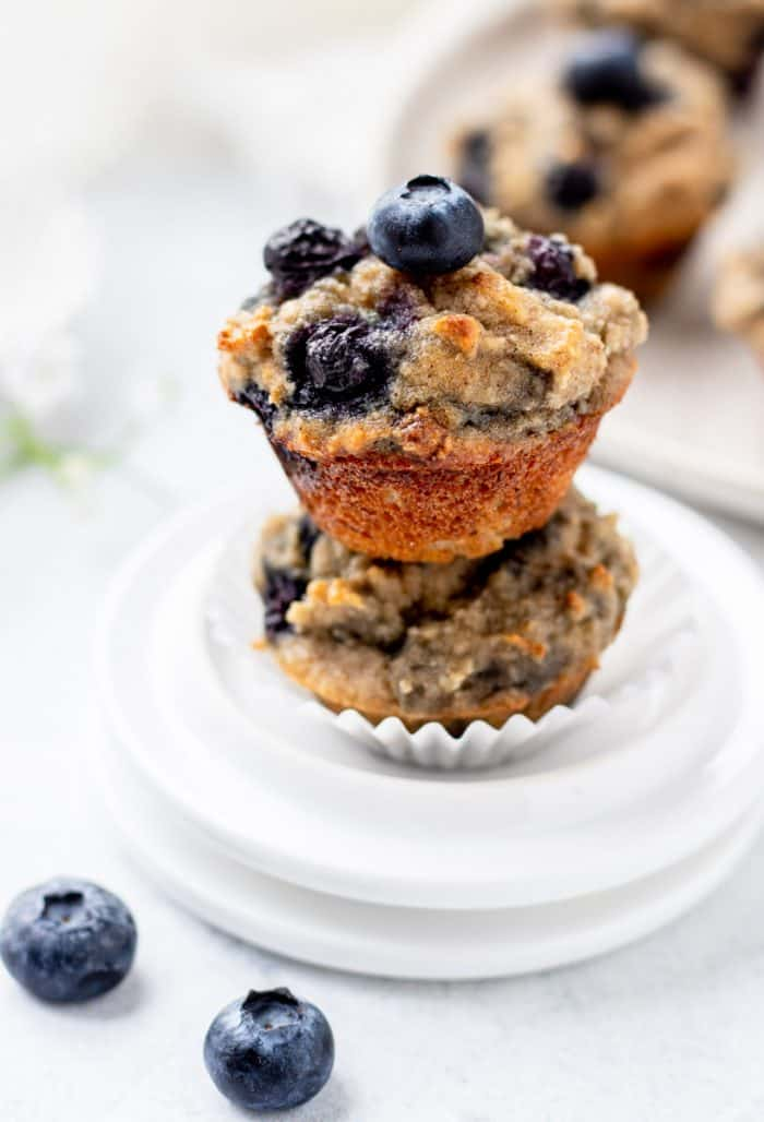 two mini almond flour blueberry muffins stacked on two white plates with fresh blueberry on top