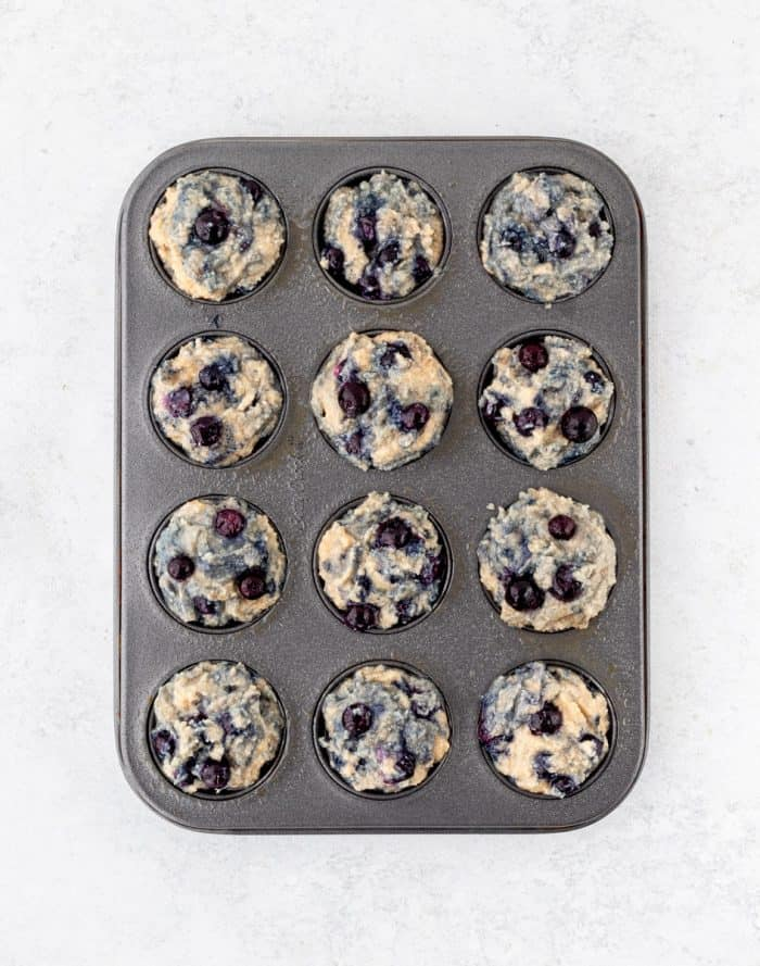 unbaked blueberry muffin batter in muffin tin