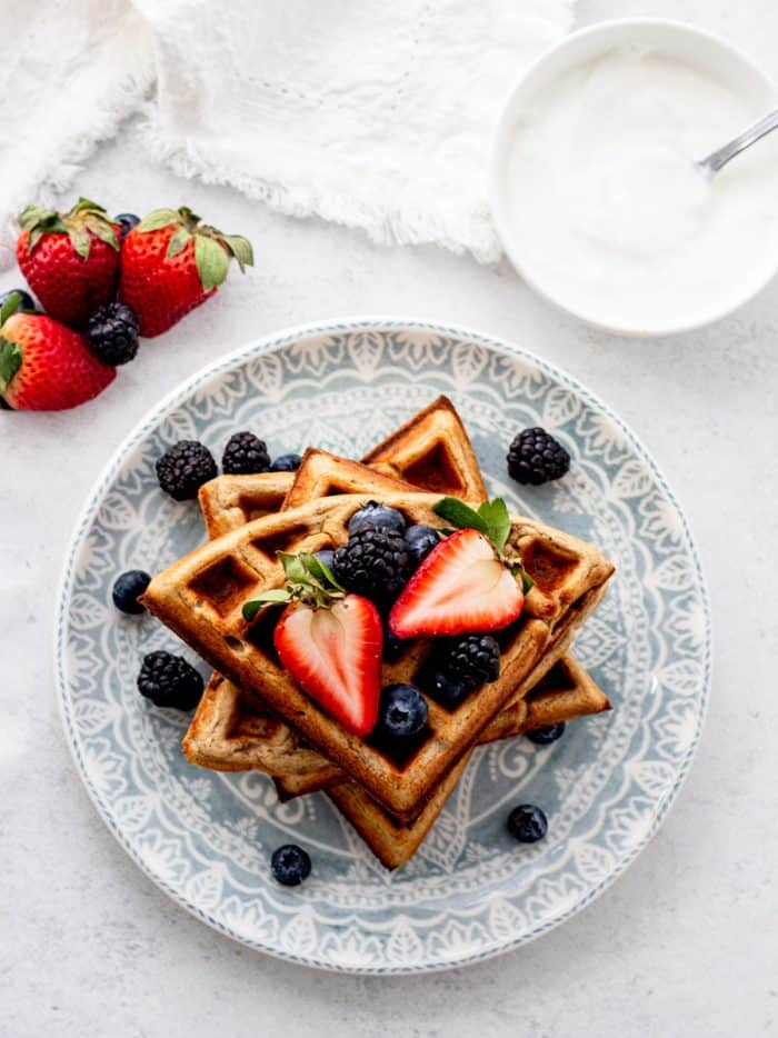 A stack of waffles on a blue plate.