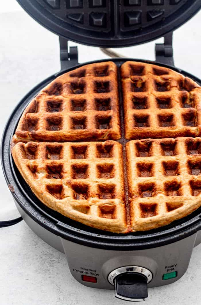 The cooked oatmeal waffles in a waffle iron.