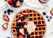 Overhead shot of oatmeal waffles with fresh berries and yogurt.
