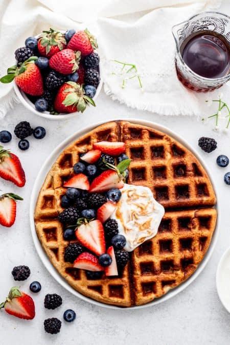 Overhead shot of oatmeal waffles with fresh berries and yogurt.