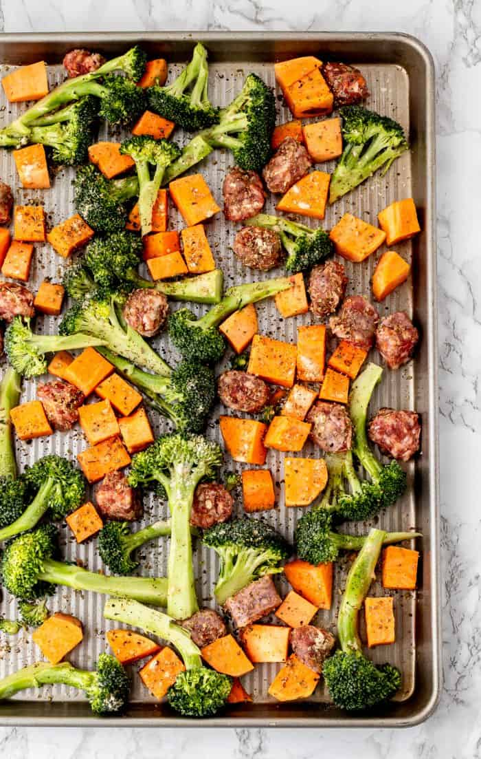 The vegetables and sausage on a sheet pan before being cooked.