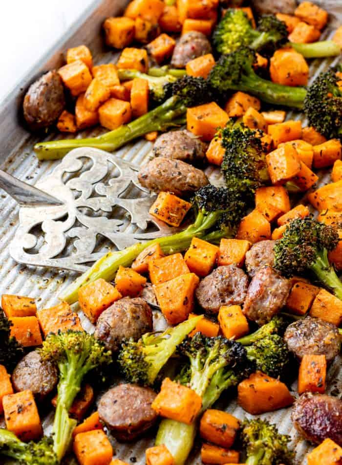 A spatula on a sheet pan with the cooked sausage and veggies.