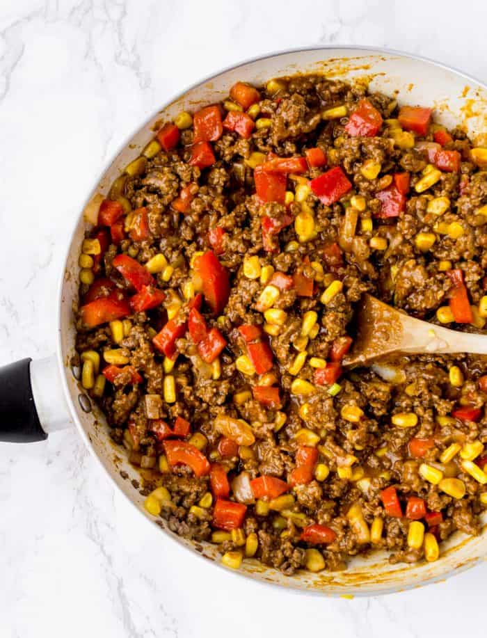taco meat mixture in a frying pan with a wooden spoon
