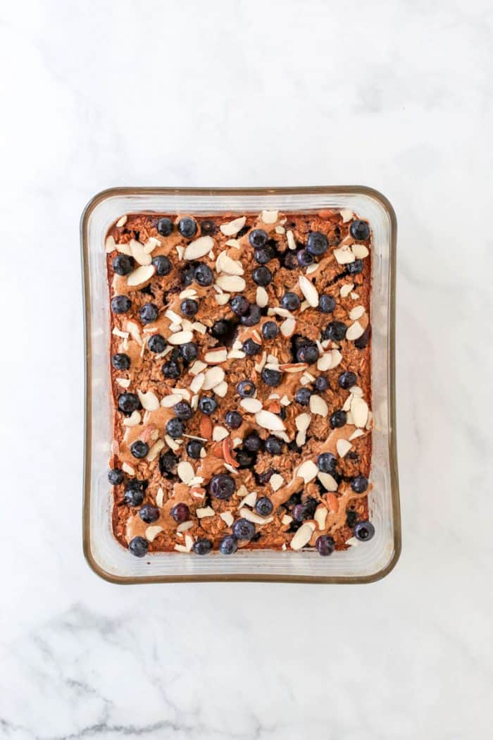 The oatmeal in a glass dish topped with fresh blueberries, sliced almonds and almond butter.
