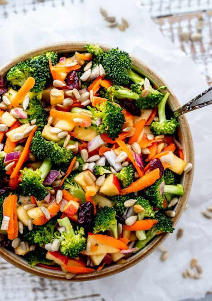 overhead shot of broccoli salad in a bowl with fork and sprinkle of sunflower seeds