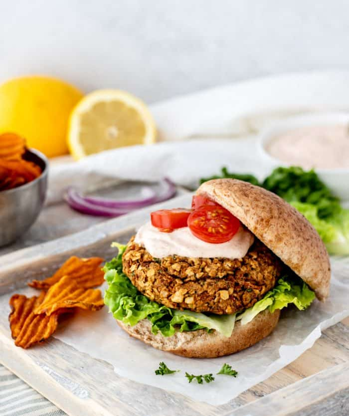 A chickpea burger with the top bun placed to one side.