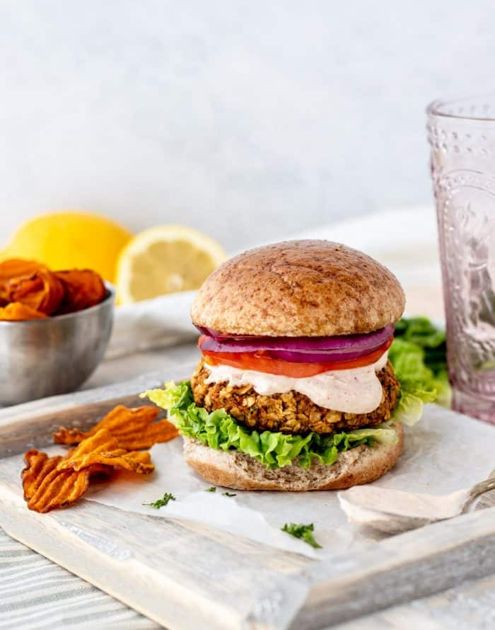 A chickpea burger patty served in a bun and topped with tahini sauce.