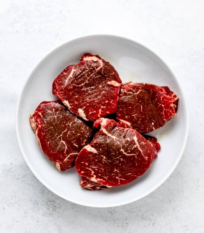 Four steaks in a large white bowl.