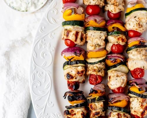 Four Greek chicken skewers on a white plate.