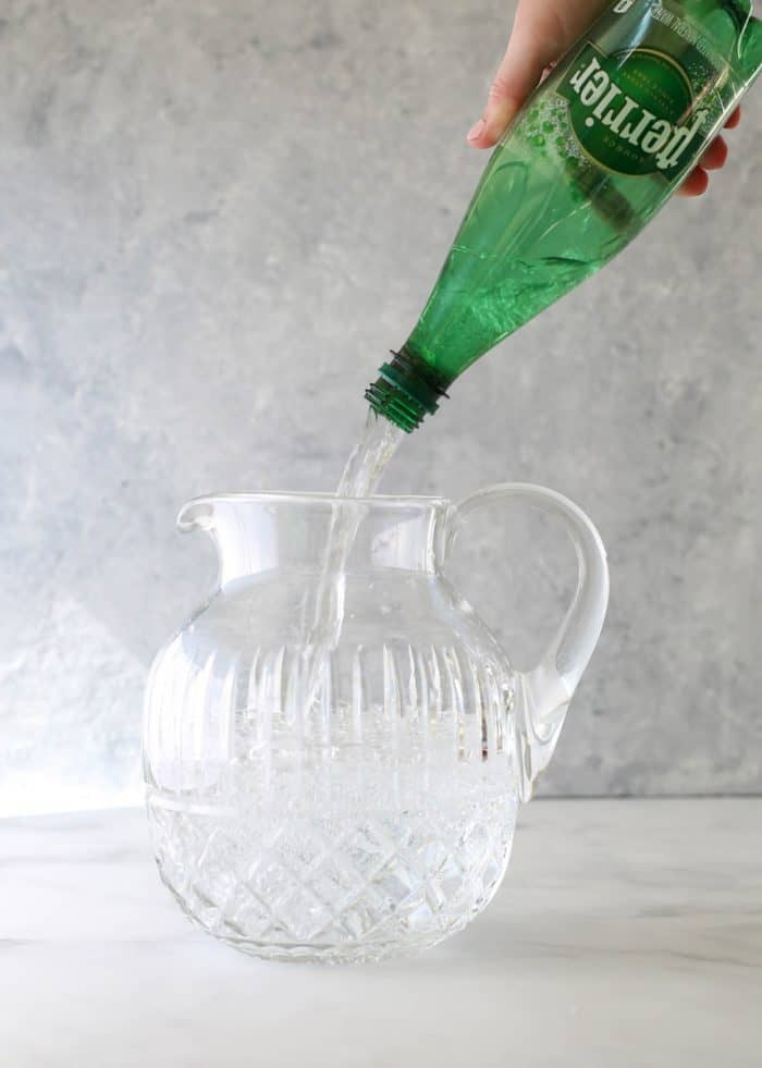 Pouring the sparking water into a pitcher.