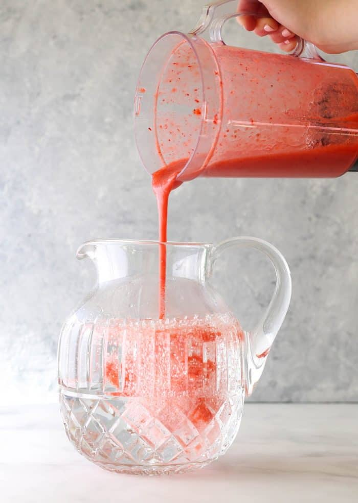 Adding the strawberry puree to the water in the pitcher.