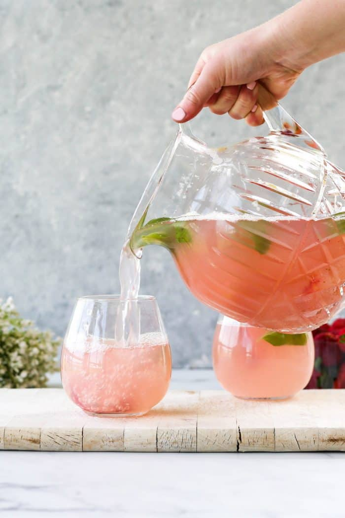 Pouring the strawberry mocktail spritzer into a glass.
