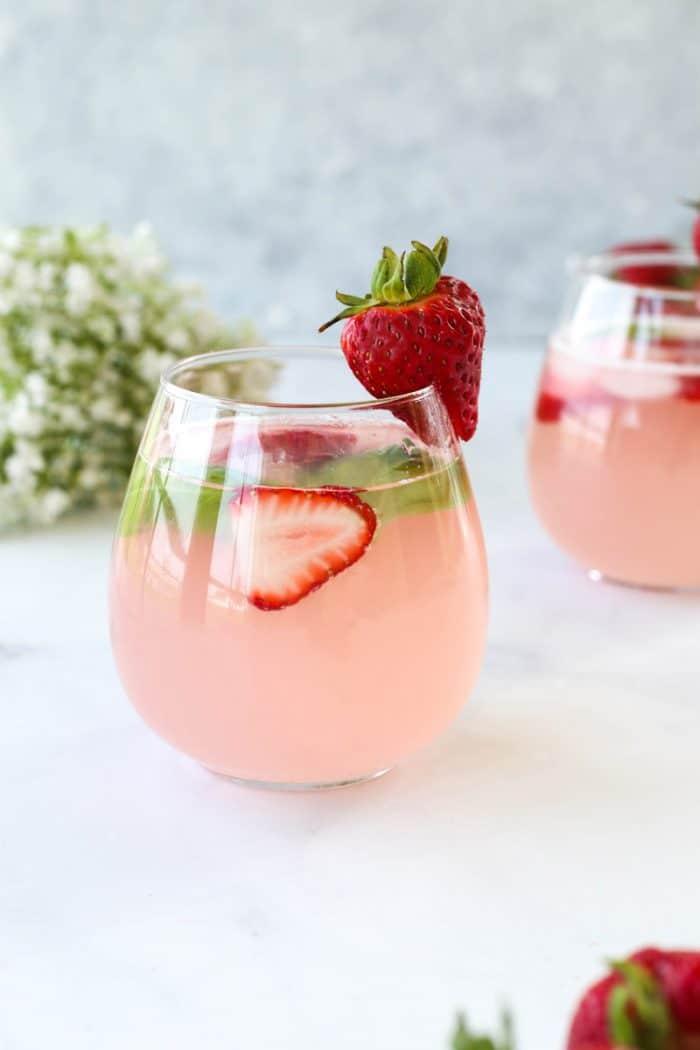 The strawberry mocktail in a glass garnished with fresh srawberries and basil leaves.