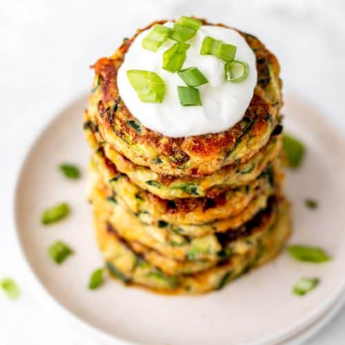 Zucchini fritters stacked on a white plate with a dollop of sour cream.