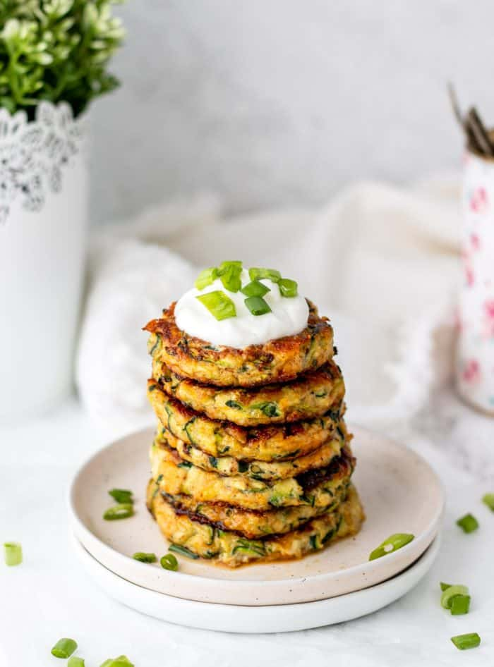 Six zucchini patties topped with sour cream and sliced scallions.