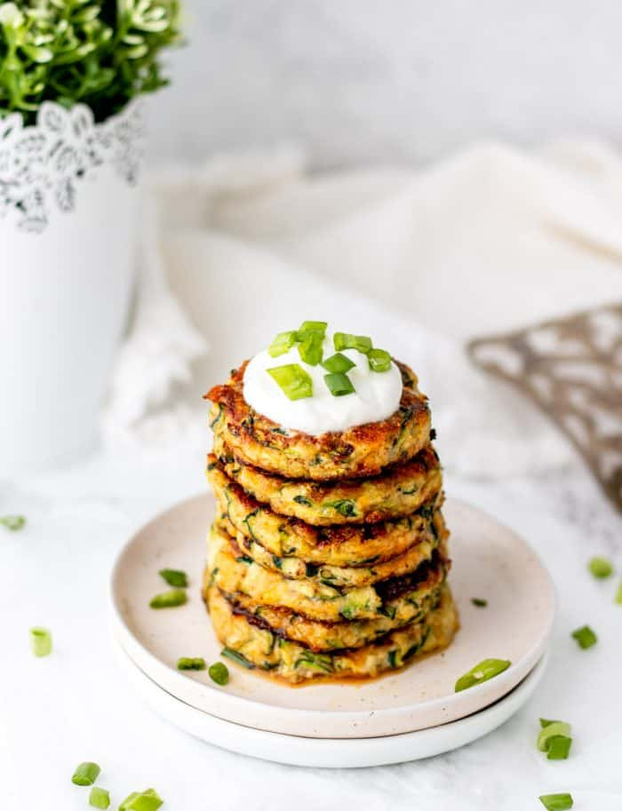 Six healthy zucchini fritters stacked on top of each other and garnished with sour cream and green onions.