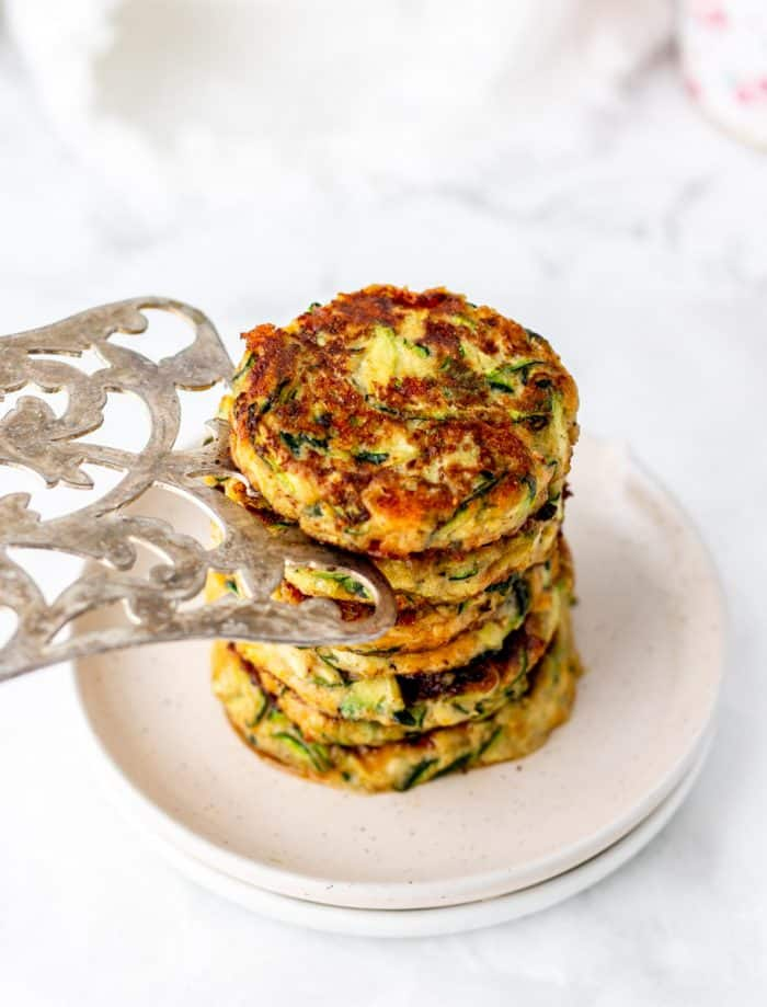 Stacking the zucchini fritters on to a plate with a metal spatula.
