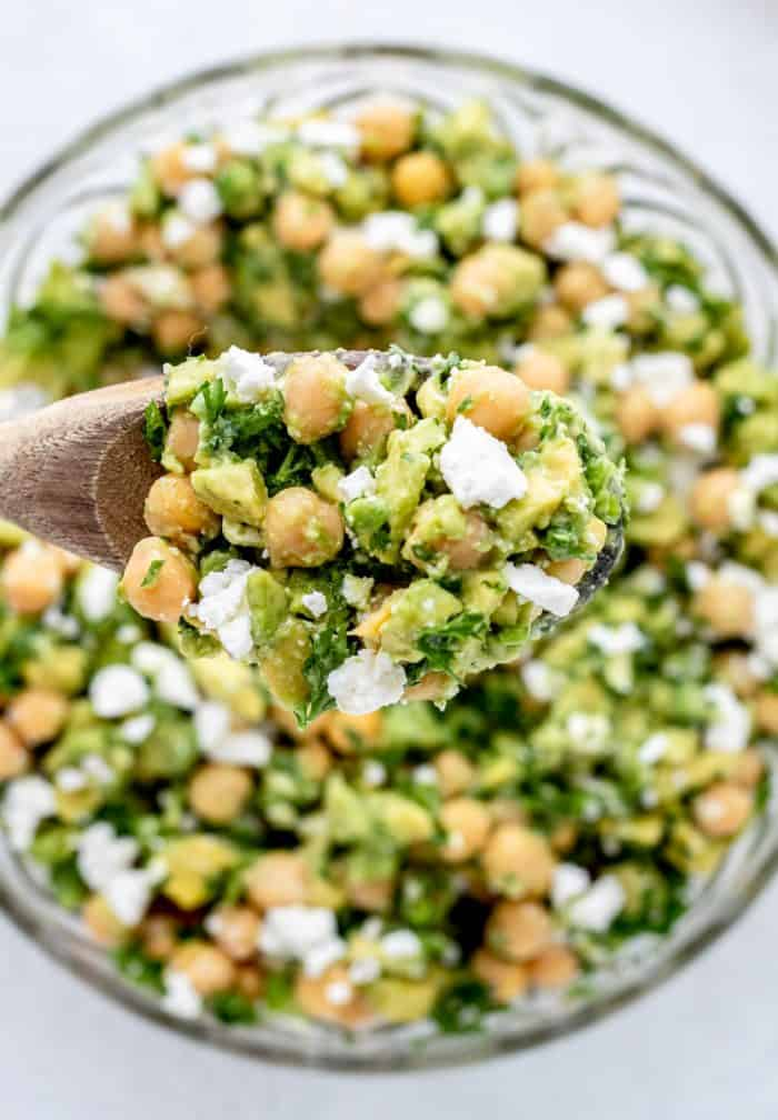 Chickpea feta salad on a wooden spoon.