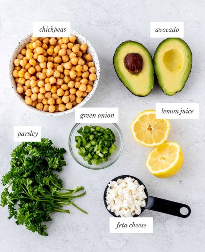 ingredients required for simple chickpea salad on grey background with labels