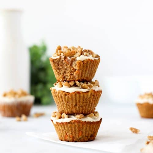 Three carrot cake muffins stacked on top of each other.