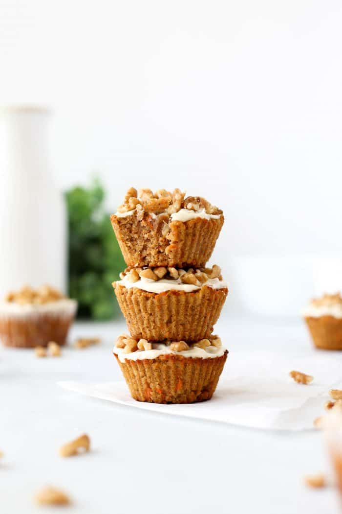 Three carrot cake muffins stacked on top of eachother.